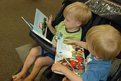 Two boys in stroller reading board books