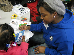 AmeriCorps member reads a book to little girl at shelter
