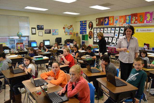 Teacher in classroom with middle school kids and Chromebooks