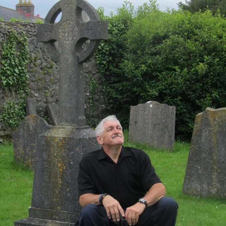 Ron leaning against a stone cross in a graveyard