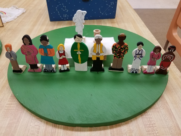Small, painted people in front of an altar table