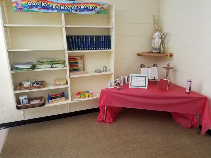 Table covered with red cloth, candles, and prayer cards. Bookshelves with abacus, stamps, Playdoh, and more.