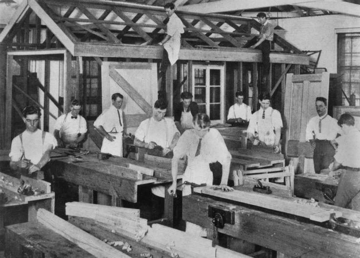 Men in ties in a carpentry workshop
