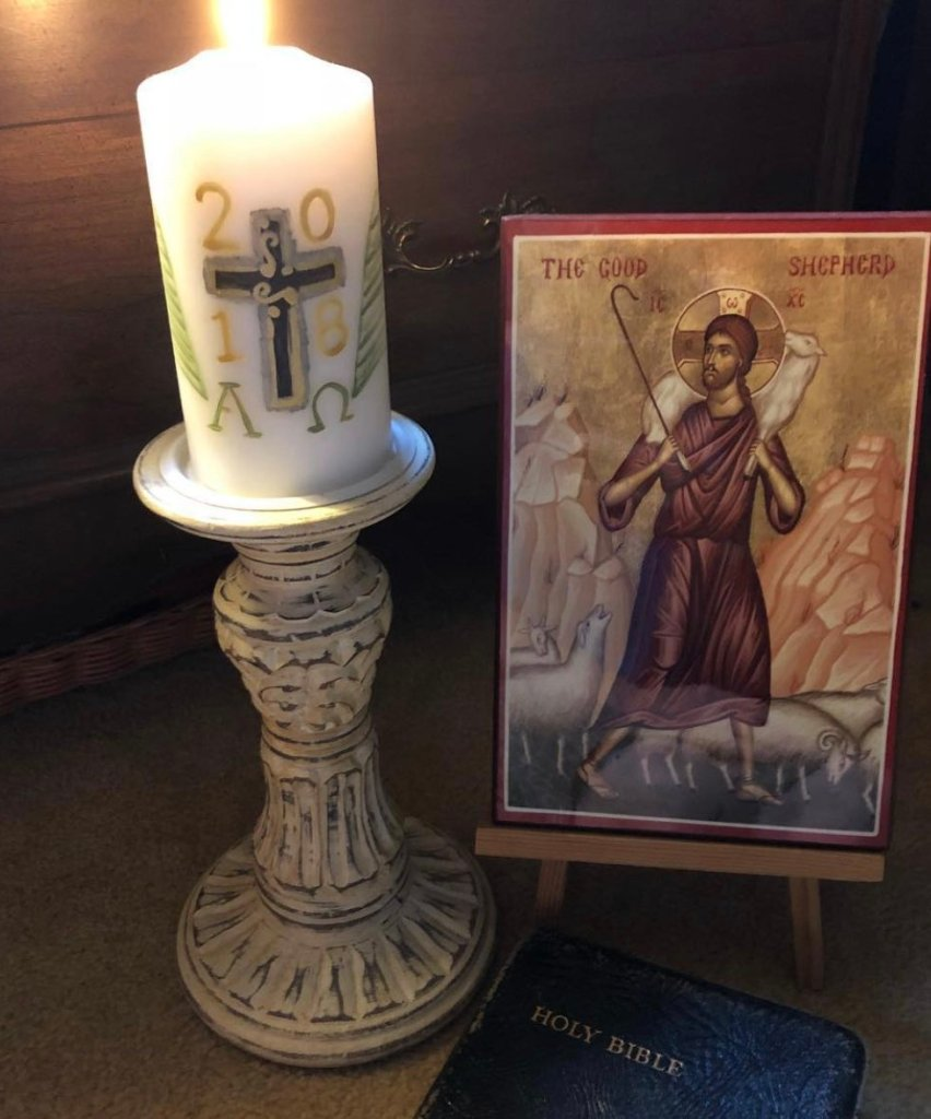 Pillar candle and icon of the Good Shepherd